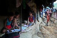 Children read books inside their makeshift tent at a camp for Rohingya people in Ukhiya.