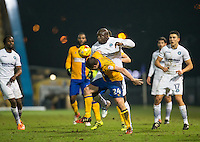 Adebayo Akinfenwa of Wycombe Wanderers battles Jamie McGuire of Mansfield Town during the The Checkatrade Trophy  Quarter Final match between Mansfield Town and Wycombe Wanderers at the One Call Stadium, Mansfield, England on 24 January 2017. Photo by Andy Rowland.