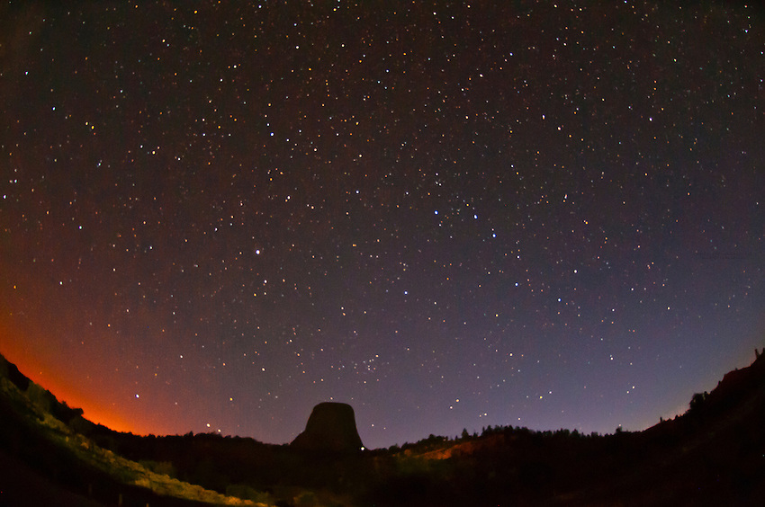 The 867 foot tall Devils Tower (a granite monolith which is a sacred site to American Indians) with a starry sky at night, Devils Tower National Monument, Wyoming USA
