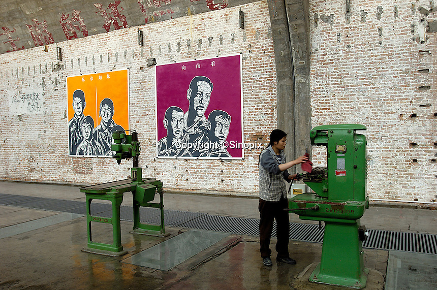 A woman cleans an old machine tools at a gallery in Factory 798 Space in the Dashanzi art district in northeast of Beijing, China. 798 is not only a showcase of contemporary Chinese art, it may also evolve into a core zone of international art, like Soho in New York. .28 Apr 2006