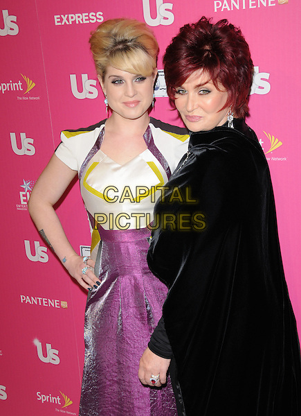 KELLY OSBOURNE & SHARON OSBOURNE.The Annual US Weekly Hot Hollywood Event held at The Colony in Hollywood, California, USA..November 18th, 2010.half length dress silk satin white purple yellow hair up sweeping fringe pink hand on hip black mom mum hand arm pointing mother daughter family cape side.CAP/RKE/DVS.©DVS/RockinExposures/Capital Pictures.