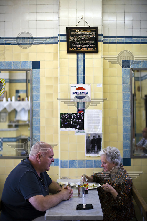 Mrs Emily Mackay, 88 eating pie and mash as a birthday treat with her son in F Cooke's Pie and Mash shop in Broadway Market, Hackney, London.