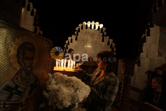 A Palestinian Orthodox Christian woman lights a candle in a church during Christmas celebrations on January 7, 2013 in Gaza City. The Orthodox Church celebrates Christmas and other religious holidays according to the Julian calendar, while other Christian churches have adopted the later Gregorian calendar. Photo by Ashraf Amra