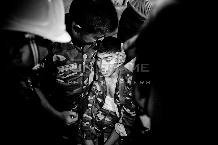 A young Bangladeshi Army officer cries after the fire inside of the collapsed building. Savar, near Dhaka, Bangladesh