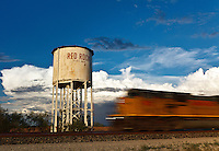 A freight train passes a water tower at Red Rock, Arizona.