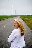 Blonde woman in white shirt standing on empty road