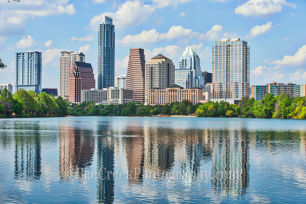 Austin skyline from across ladybird lake with the reflection of the downtown buildings and puffy white clouds all reflected in the water.  You can view all the iconic city buildings like the frost, austonian which make up the modern urban cityscape that is Austin today.