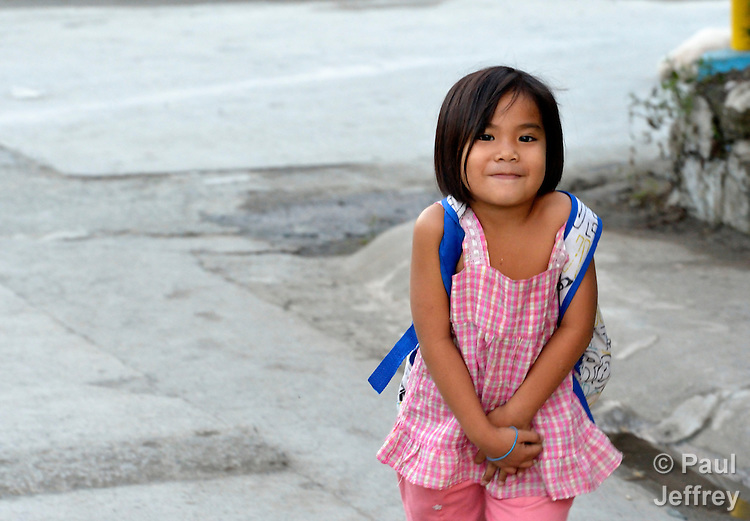 A girl walks home from school in the Suburban neighborhood of Rodriguez, Rizal, in the Philippines. Most of the community's families were relocated here from other area of Manila and the nearby countryside to make way for urban renewal projects or to move them out of harm's way. Yet the new community was hit hard by Typhoon Ketsana in 2009, and Christian Aid, a member of the ACT Alliance, provided emergency relief supplies. Over the years since, with help from Christian Aid and other groups, community members have organized themselves and engaged in a process of disaster risk reduction, including identifying and mapping high-risk zones and evacuation routes in their area. Christian Aid has also assisted with financial and technical support for income generating livelihood projects and community enterprises.