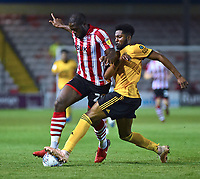 Lincoln City's John Akinde vies for possession with Wolverhampton Wanderers U21's Cameron John<br /> <br /> Photographer Andrew Vaughan/CameraSport<br /> <br /> The EFL Checkatrade Trophy Northern Group H - Lincoln City v Wolverhampton Wanderers U21 - Tuesday 6th November 2018 - Sincil Bank - Lincoln<br />  <br /> World Copyright © 2018 CameraSport. All rights reserved. 43 Linden Ave. Countesthorpe. Leicester. England. LE8 5PG - Tel: +44 (0) 116 277 4147 - admin@camerasport.com - www.camerasport.com