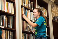 Angela Nardi,'21, organizes books at the Redwood Library as she participate in the Salve Regina University Exploration Day of Service in Newport.