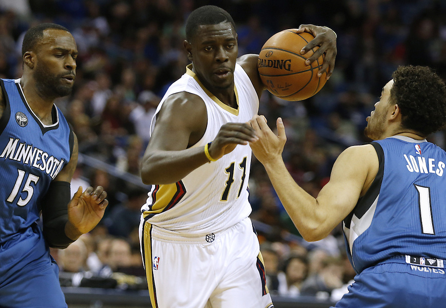 New Orleans Pelicans guard Jrue Holiday (11) drives against Minnesota Timberwolves forward Shabazz Muhammad (15) and guard Tyus Jones (1) during the first half of an NBA basketball game Saturday, Feb. 27, 2016, in New Orleans. (AP Photo/Jonathan Bachman)