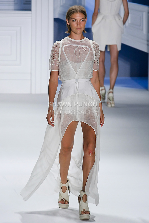 Arizona Muse walks runway in a White textured gauze carved hem gown with Dudley sleeve and white mackintosh cotton double layer drawstring peplum, and White striped linen-silk bustier, by Vera Wang, for the Vera Wang Spring 2012 collection, during Mercedes-Benz Fashion Week Spring 2012.