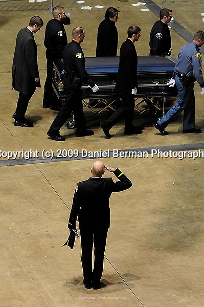 An officer salutes as a casket is removed following a memorial service for four slain police officers in Tacoma, WA Tuesday December 8, 2009. The memorial brought an estimated 20,000 police officers and community members to the area.