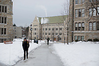 People walk along sidewalks on the campus of Boston College in Chestnut Hill, Massachusetts, campus on Tues., Dec. 17, 2013.