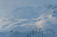 The morning sun breaks through the clouds over Alpine ski slopes blanketed in thick snow
