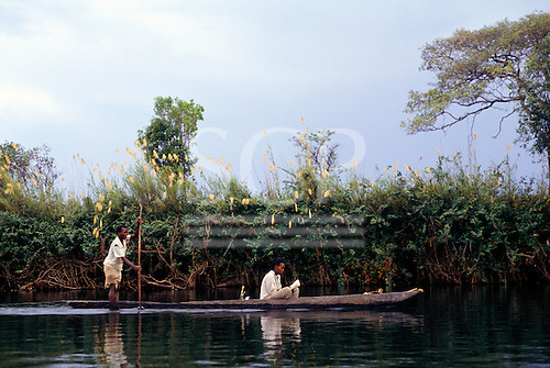 Zambia. Zambian woman in a dug out canoe reading with man polling the canoe.