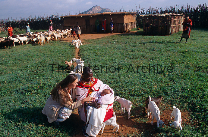 Anna and her baby with a Masai herder and his goats