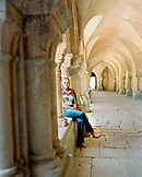 FRANCE, Burgundy, young woman sitting in Abbaye De Fontenay, Marmagne