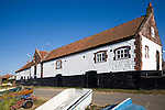 Whitewashed boathouse at the coastal village of Burnham Overy Staithe, north Norfolk coast, England