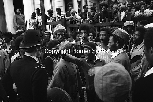 Notting Hill, London. 1976<br /> At the Notting Hill Carnival a peaceful group of Rastafarians drumming and chanting were broken up and moved on by the police. A furious young Rastafarian lets the police know what he thinks, as an Elder wills him to calm down. <br /> <br /> <br /> <br /> Victor Romero-Evans to right of angry youth he is wearing a  woolen hat stretched over a trilby
