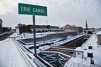 LOCKPORT, NEW YORK -  Jan 10: The Erie Canal runs through the center of the City of Lockport, New York, as seen here from the bridge on Pine Street looking South West over the locks towards Lake Erie (to the right) and South towards Main street (left) in downtown Lockport. During the winter months the canal is drained, so that the frozen water does not damage the locks. The Erie Canal is an artificial waterway in New York that runs about 363 miles from Albany on the Hudson River to Buffalo at Lake Erie, completing a navigable water route from the Atlantic Ocean to the Great Lakes. First proposed in 1808, it was under construction from 1817 to 1832 and officially opened on October 26, 1825. It was the first transportation system between the eastern seaboard (New York City) and the western interior (Great Lakes) of the United States that did not require portage, was faster than carts pulled by draft animals, and cut transport costs by about 95%. The canal fostered a population surge in western New York state, opened regions farther west to settlement, and helped New York City become the chief U.S. port. It was expanded between 1834 and 1862. In 1918, the original canal was replaced by the larger New York State Barge Canal. Today, it is part of the New York State Canal System. In 2000, the United States Congress designated the Erie Canalway National Heritage Corridor to recognize the national significance of the canal system as the most successful and influential human-built waterway and one of the most important works of civil engineering and construction in North America.  (Photo by Landon Nordeman)