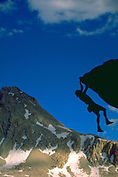 Silhouette of a climber hanging on precariously by two hands to a rocky outcropping beneath Mount Hexley in the Evolution Peaks region in Kings Canyon National Park, California with blue sky in the distance.