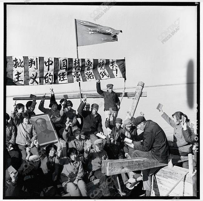 "Like Red Guards across the country, fishermen along the upper Songhua River on the outskirts of Harbin eagerly demonstrate their devotion to Mao, criticizing ""Liu Shaoqi's revisionist line"" with a banner and portraits of Mao. Bayan county, Heilongjiang province, 8 July 1967"