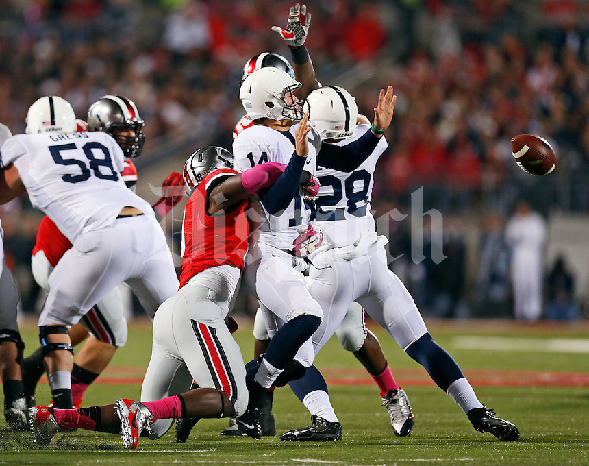 Ohio State Buckeyes defensive lineman Noah Spence (8) forces a fumble by Penn State Nittany Lions quarterback Christian Hackenberg (14) during the first half of the NCAA football game at Ohio Stadium in Columbus on Oct. 26, 2013. (Adam Cairns / The Columbus Dispatch)