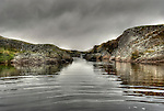 Calm water in cove under grey skies