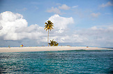 INDONESIA, Mentawai Islands, Kandui Surf Resort, a surfer walking on a small island against a cloudy sky