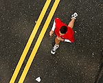 A participant seen from above wearing red, runs close to the double yellow line on Kelly Drive during the Philadelphia Marathon in Philadelphia, Pennsylvania on November 19, 2006.