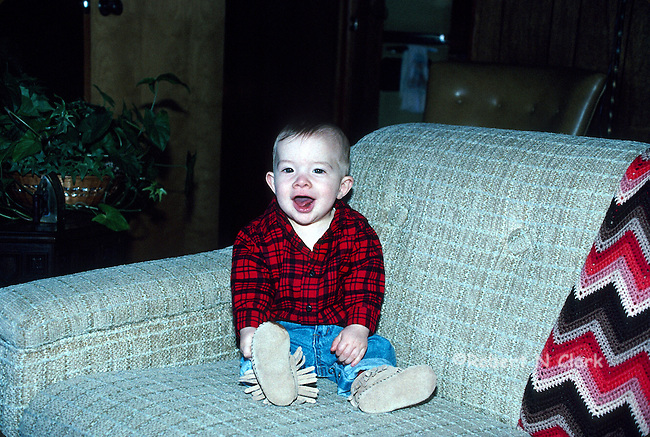 Boy on sofa with red plaid shirt, jeans and mocassins