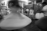 Under the strident sound of the drums, Umbanda followers dance and sing as the invoke spirits during a spiritual session in a temple in Montevideo Uruguay. Mae Shirley de Xango and her assistants act as mediums in order to connect with the spirits to whom the believers will ask for fulfilment of their wishes and help. Photo by Quique Kierszenbaum.