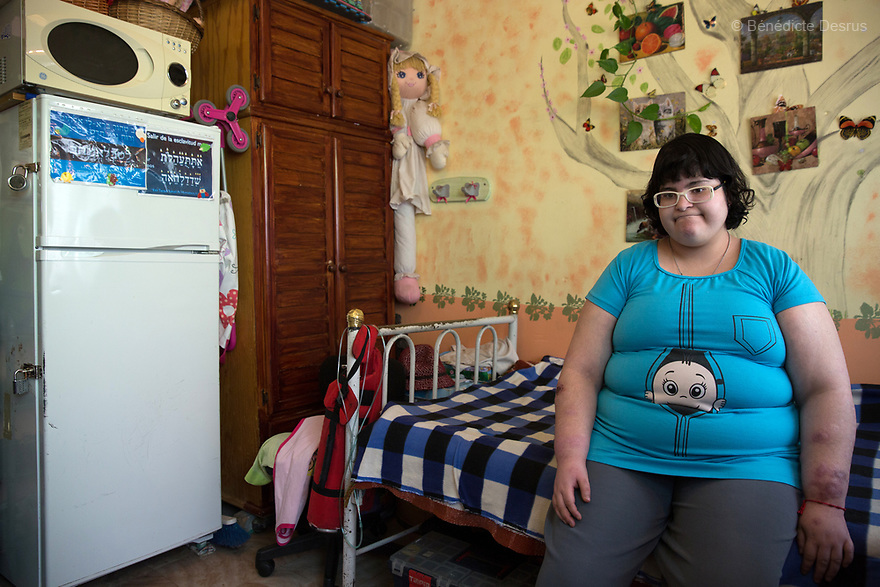 Citlalli poses for a portrait while sitting on her bed, which is located next to a locked refrigerator in her two-room home in Mexico City, Mexico on March 23, 2017. Because of her condition, her mother keeps the refrigerator and kitchen under lock and key. Delia Citlalli Pineda Corzo, a 21-year-old Mexican girl, lives with her 42-year-old mother Diana Cristina Corzo Zárate in a two-room apartment in Mexico City. She was diagnosed with Prader-Willi syndrome at age four. At age 15, doctors detected that she had diabetes. Citlalli weighs 106 kilos (233.6 pounds) and stands 150 centimeters (4 feet 11 inches). She has a BMI of 50.5, making her morbidly obese. She also suffers from sleep apnea. Citlalli lacks the faculty of speech and cannot read, but her mother says they have developed their own form of communication. Prader-Willi Syndrome (PWS) is a rare genetic disorder caused by an abnormality in chromosome 15. In newborns symptoms include weak muscle tone (hypotonia), poor appetite and slow development. In childhood the person experiences a sensation of constant hunger no matter how much he/she eats which often leads to obesity and Type 2 diabetes. There may also be mild to moderate intellectual impairment and behavioral problems. Physical characteristics include a narrow forehead, small hands and feet, short in stature, and light skin color. Prader-Willi syndrome has no known cure. However, with early diagnosis and treatment such as growth hormone therapy, the condition may improve. Strict food supervision is typically required. PWS affects an estimated 1 in 10,000 to 30,000 people worldwide. (Photo by Bénédicte Desrus)