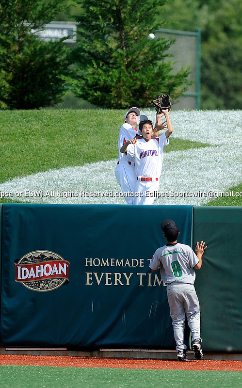 Dustin Imanaka can only watch as two fans try to snare a home run ball during the United States Championship game at the Cal Ripken World Series in Aberdeen, Southeast Lexington (KY) defeated Oahu East (HI) to win the US championship and earn a chance to play for the world championship, Maryland on August 20, 2011