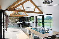 The kitchen and dining room sit within an open-plan space with large windows to the front and back. The kitchen features an island on wheels, which can be used as a breakfast bar or serving station. The stools are vintage the chairs are by Arne Jacobsen. The design makes the most of the views and the connections with the outdoors, within a free-flowing fluid floor plan.
