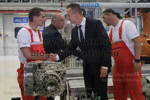 Hungary's minister of foreign affairs and trade Peter Szijjarto (2nd R) and Peter Kossler (2nd L) production and logistics director of Audi AG shake hands with workers at the E-Engine production start of electric engines at the Audi car factory in Gyor (about 120 km West of Budapest), Hungary on July 24, 2018. ATTILA VOLGYI