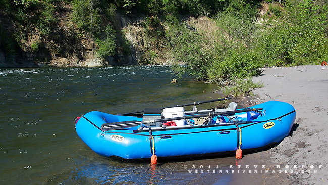 A blue NRS raft on a beach along the Sandy River.