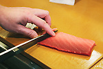 """Tokyo, Japan - Japanese Sushi Chef, Nogami Shinji slices raw fish with his very sharp knife : Japanese Sushi Chef, Nogami Shinji, established his own Sushi restaurant in 2001 called """"Nogami"""" in the Hacchobori district of Tokyo. He started his career 25 years ago and continues to master the culinary craft to make the perfect sushi. His father, also a sushi chef, and his son who is currently in training to become a sushi chef shows illustrate how the art of making sushi has been passed down through generations. Nogami's day begins in the very early morning hours when he selects fish at the Tsukiji market. Choosing the best fish is considered the most important part of his work and he makes sure that he always has about 30 different varieties from which to serve. His restaurant is open late until 10pm and many regulars stay even later so Nogami will usually take an afternoon sleep break between 2pm-5pm when the restaurant is closed. ....Nogami-san's hobby is also fishing and he lives in the Tokyo Bay area so can do this in his free time. He usually releases what he catches though as he is worried that the Tokyo Bay water is not so clean. His son trains, works and sleeps at a different restaurant which is normal for a junior. As he improves his technique he will start to help more in his father's restaurant and eventually take over. There are no exams or text books for sushi chefs so this learning is all based on experience. Nogami's wife also helps out in the restaurant when she has time when their young daughter is at school.....Nogami often serves non-Japanese customers and he is surprised that """"They can eat anything and they often use heaps of wasabi"""". He is proud of his """"Aritsugu"""" knife which is worth about $700 and his most important tool. ....Nogami-san is worried that since the great March 11 earthquake and tsunami, the cost of fish has soared. (Photo by Yosuke Tanaka/AFLO)"""