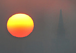 The bright orange fireball appeared out of the haze and light fog seen from Vista Point lookout on the north side of the Golden Gate Bridge looking towards the Transamerican Pyramid and the San Francisco skyline.