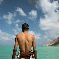 Dec. 24, 2014 - Socotra, Yemen. Fathi on a boat crossing the Detwah Lagon. Fathi helps his mother cook and gives tours to visitors around the lagon. Socotra draws very few tourists, the last few years Socotra as averaged about 3000 tourists a year, with a fall in 2014 due to political instability on the main land. ©Nicolas Axelrod / Ruom