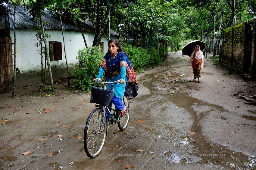 Jesmin Akhter, 26 (in turquoise & blue), cycles through the village in one of her 'marketplaces', Jerai Villlage, Gobindagonj Upazila, Gaibandha, Bangladesh on 19th September 2011. She has found financial independence and contributes to her household income by working as a saleswoman, earning 3500 - 5000 Bangladeshi Taka per month. She is the top saleswoman under her 'hub', out of 30 women. Having worked for about 2.5 years, she cycles from village to village and door to door in a country where women on bicycles is an extremely uncommon sight. She is one of many rural Bangladeshi women trained by NGO CARE Bangladesh as part of their project on empowering women in this traditionally patriarchal society. Named 'Aparajitas', which means 'women who never accept defeat', these women are trained to sell products in their villages and others around them from door-to-door, bringing global products from brands such as BATA, Unilever and GDFL to the most remote of villages, and bringing social and financial empowerment to themselves.  Photo by Suzanne Lee for The Guardian