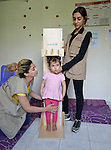 Maha Shoker and Maha Haidar, health workers with International Orthodox Christian Charities, a member of the ACT Alliance, use an infantometer to measure 3-year old Nazha, a Syrian refugee child, in the community health center in Kab Elias, a town in Lebanon's Bekaa Valley which has filled with Syrian refugees. Lebanon hosts some 1.5 million refugees from Syria, yet allows no large camps to be established. So refugees have moved into poor neighborhoods or established small informal settlements in border areas. International Orthodox Christian Charities provides support for the community clinic in Kab Elias, which serves many of the refugees. <br /> <br /> PARENTAL CONSENT OBTAINED.