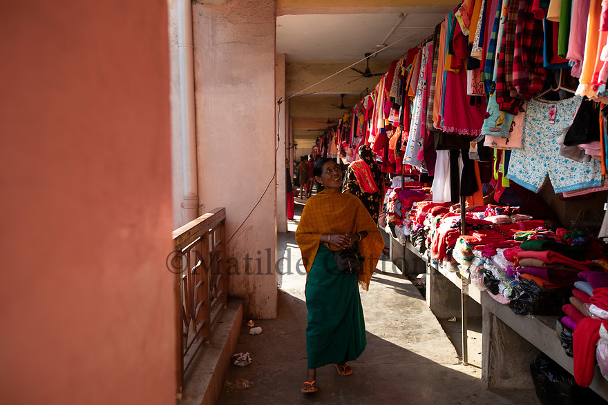 India - Manipur - Imphal - A client walks in the market aisle early in the morning looking at the textiles.