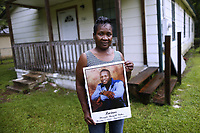 Alma Dunning, mother of Lucious Bolton, holds a photo of her son as she poses for a photo in front of the house where Bolton grew up in Moss Point, Mississippi, Friday, August 31, 2018. Lucious Bolton is one of 16 Mississippi inmates between the ages of 24 and 75 who died while in state custody in August; a figure that has renewed concerns about the state's treatment of its prisoners, including the medical care they receive.