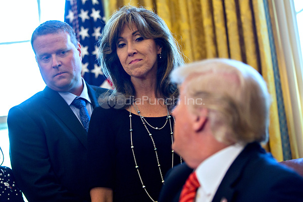 Tammie Jo Shults, a Southwest Airlines Co. captain, center, and Darren Ellisor, a Southwest Airlines first officer, left, listen as U.S. President Donald Trump speaks while meeting with the crew and passengers of Southwest Airlines Co. flight 1380 in the Oval Office of the White House in Washington, D.C., U.S., on Tuesday, May 1, 2018. An engine on Southwest's flight 1380, a Boeing Co. 737-700 bound for Dallas from New York's LaGuardia airport, exploded and made an emergency landing on April 17 sending shrapnel into the plane and killing a passenger seated near a window.<br /> Credit: Andrew Harrer / Pool via CNP /MediaPunch