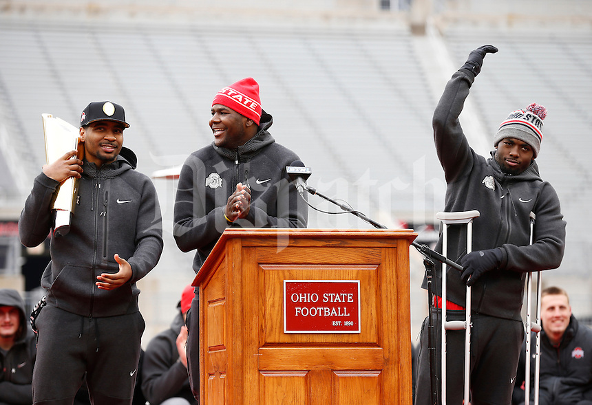 From right, Ohio State Buckeyes quarterbacks J.T. Barrett, Cardale Jones and Braxton Miller salute the crowd during the celebration for winning the national championship at Ohio Stadium on Jan. 24, 2015. (Adam Cairns / The Columbus Dispatch)
