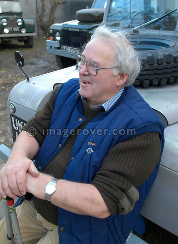 Brian Bashall, founder of Dunsfold Landrovers and the Dunsfold Collection of Land Rovers, sitting on the front bumper of a Series One Land Rover at the Dunsfold Landrovers Series 1 Parts Weekend 22-24/10/2004. --- No releases available. Automotive trademarks are the property of the trademark holder, authorization may be needed for some uses. --- The garage Dunsfold Landrovers (DLR) was established in 1968 in Dunsfold, Surrey, UK. Due to the ever growing number of Land Rover vehicles the Dunsfold Collection of Land Rovers was launched in 1993. Supported by the company Land Rover and the Gaydon Heritage Centre today Dunsfold is maintaining the biggest and most varied collection of Land Rovers in the world. Because of the enormous quantity of original spare parts for older Land Rovers that are now stored in Dunsfold, every now and then a theme-event is held.