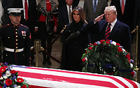 U.S. President Donald Trump salutes as he stands with First Lady Melania Trump at the flag draped casket of former U.S. President George H.W. Bush as it lies in state inside the U.S. Capitol Rotunda on Capitol Hill in Washington, U.S., December 3, 2018. <br /> CAP/MPI/RS<br /> &copy;RS/MPI/Capital Pictures
