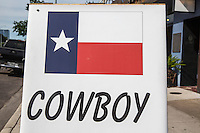 Signs and Symbols for Texas Cowboy - Texas Flag & Cowboy set in type is a retail sidewalk sign set in front of a retail store - Stock Image.